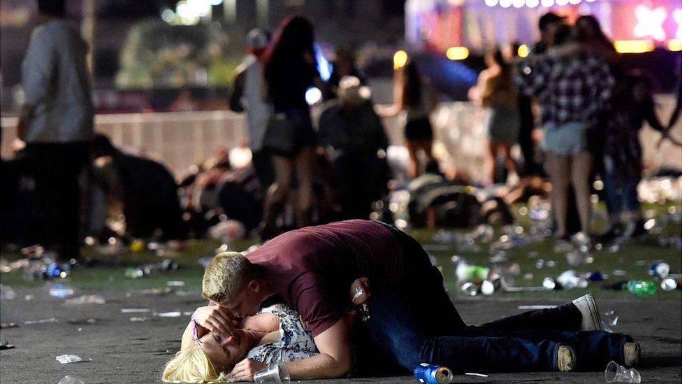Un hombre sobre una mujer tirada en el suelo en el lugar de los hechos.
