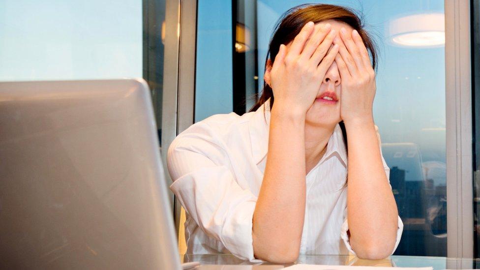 mujer usando computadora y tapándose la cara