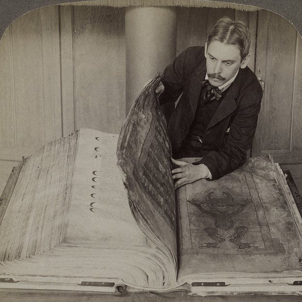Hombre abriendo la Biblia del Diablo
