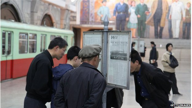People reading newspaper in North Korea