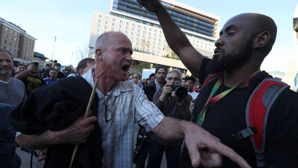 """Un seguidor de baloncesto que intenta acceder al estadio discute con un manifestante del grupo """"Las vidas de negros importan"""""""