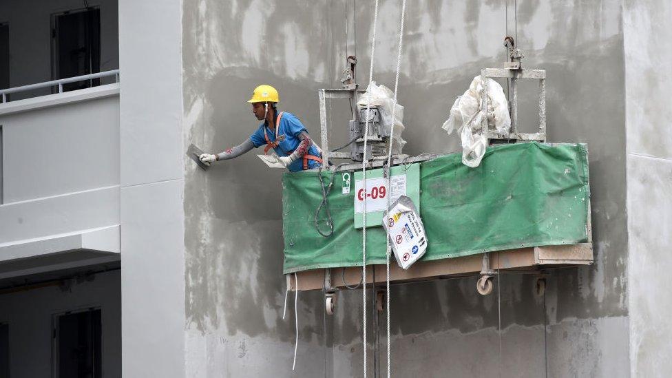Obrero aplicando cemento.