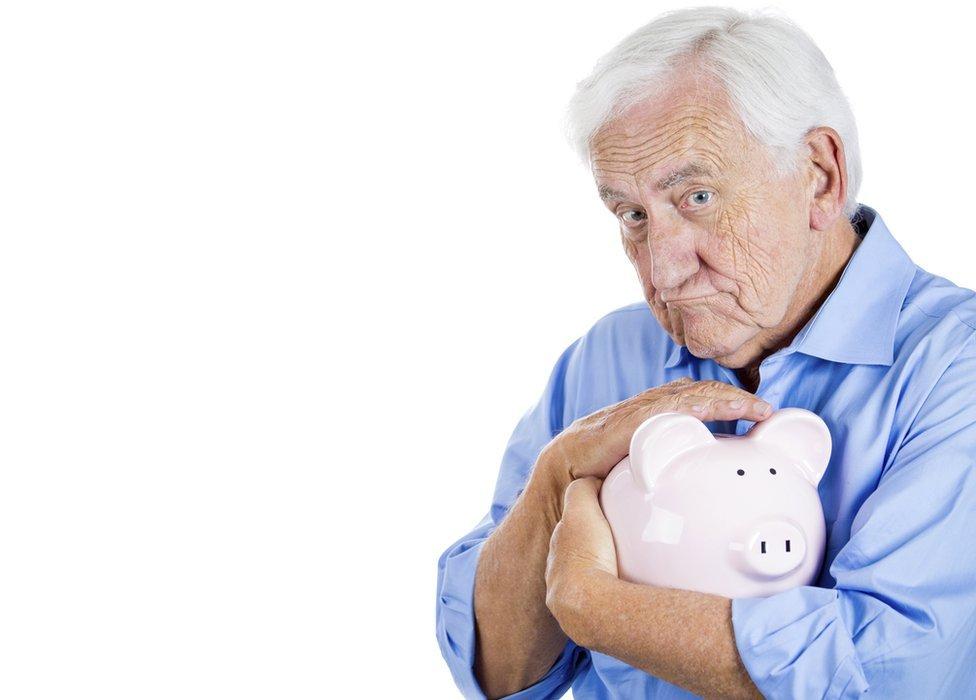 man protecting his piggy bank