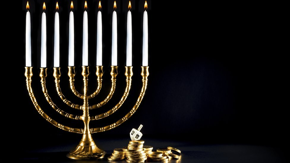 A golden menorah with dreidl and coins