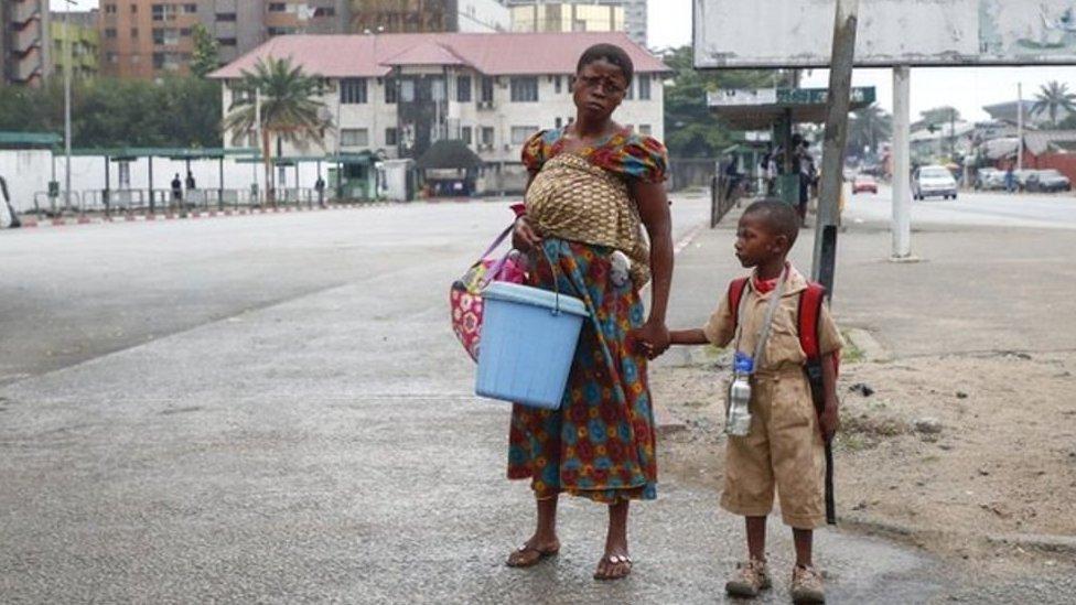 Mujer toma de la mano a su hijo que porta una mochila
