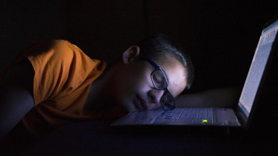 niño durmiendo sobre laptop