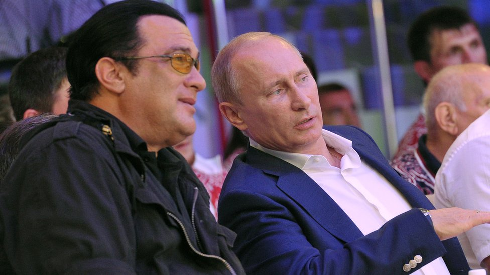 Steven Seagal sits with Russian President Vladimir Putin during a fighting championship in 2012