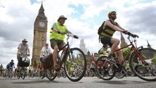 Lots of cyclists of all ages, cycling through London, Big Ben in the distance, behind them