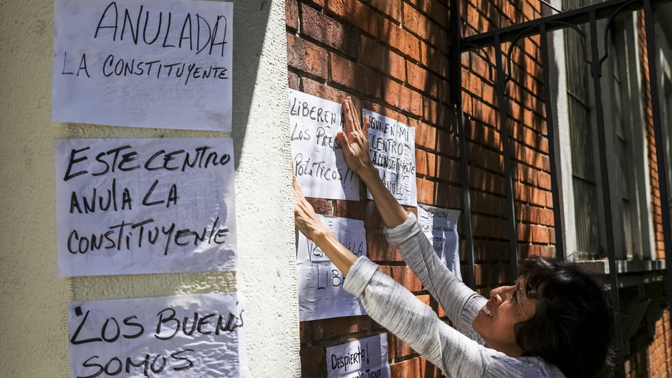 Una opositora cubre con carteles de protesta un centro de votación en Caracas.
