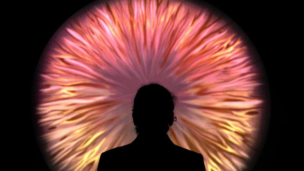 Contorno de una mujer mirando una proyección abstracta similar al iris de un ojo.