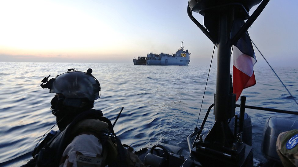 French marine commandos operate on a speed boat just off the French frigate Sirocco as part of the EU naval force combating piracy off the coast of Puntland on 26 March 2014.