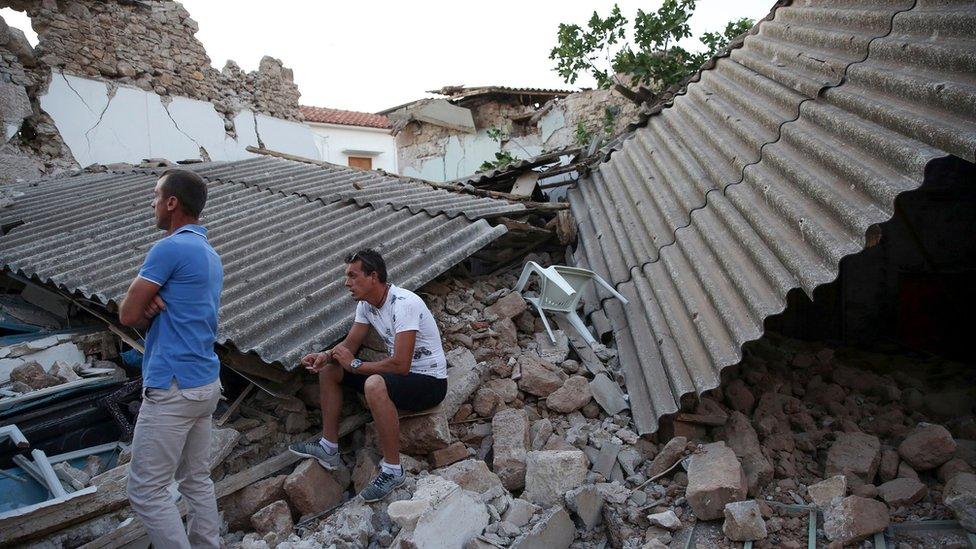 Habitantes de Vrisa parados sobre escombros.