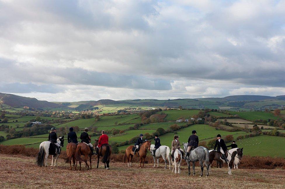 Gente a caballo en el límite entre Inglaterra y Gales.