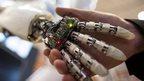 A man grasping a robot hand