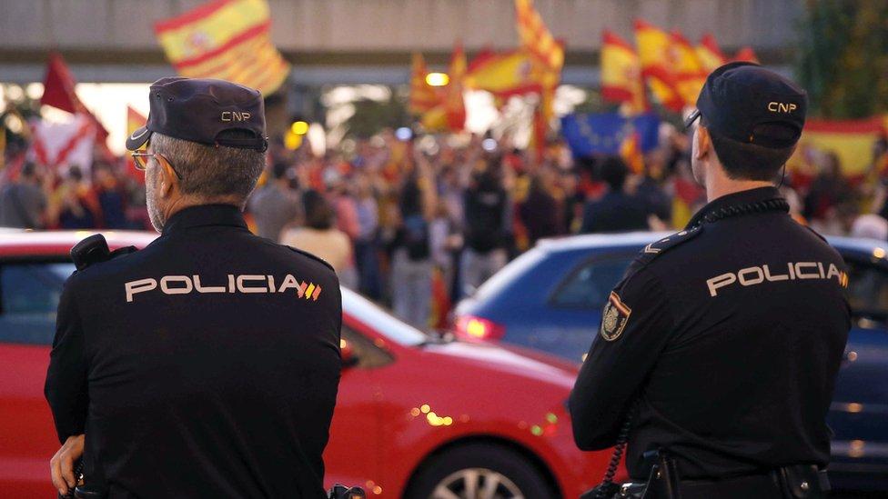 Policía mirando a gente con banderas de España, Cataluña y la Unión Europea en Barcelona.