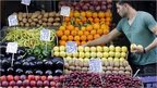A vendor displays fruits in his shop in a local market in central Athens