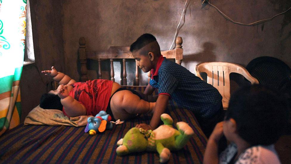 Luis Manuel en la cama jugando con su hermano Mario y su primo Michel