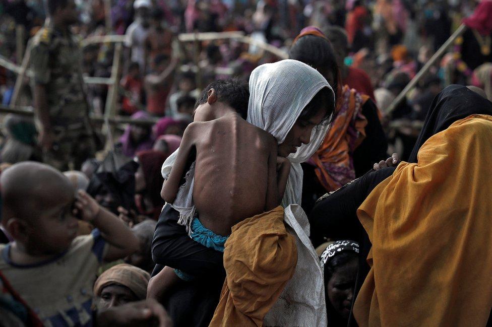 Una mujer carga a su hijo enfermo en un campo de refugiados en Bangladesh.