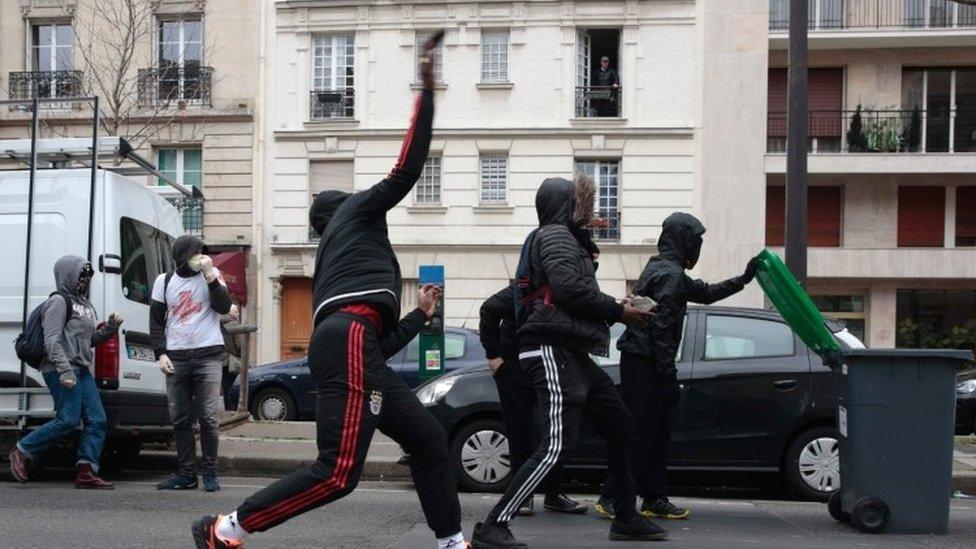 عدد من المحتجين يلقون الحجارة على رجال الشرطة