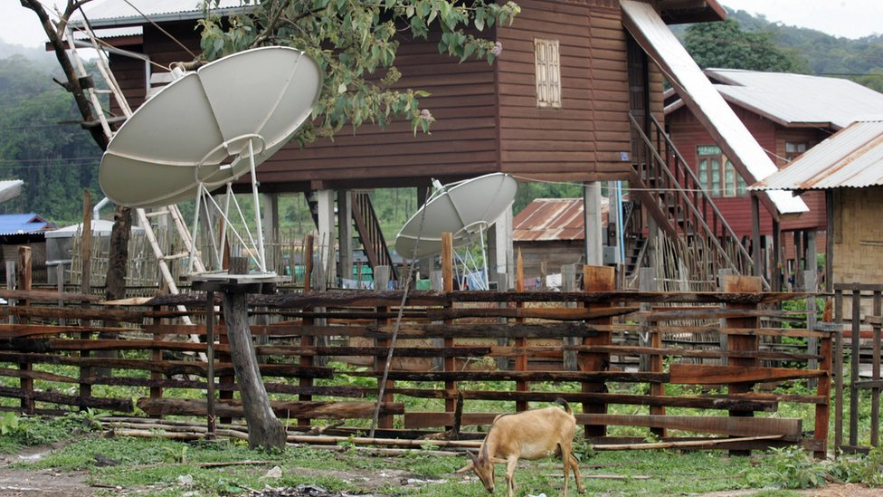 A goat eats grass near by TV satellite dishes installed outside houses at a village in the South-western Nakai plateau in Laos.