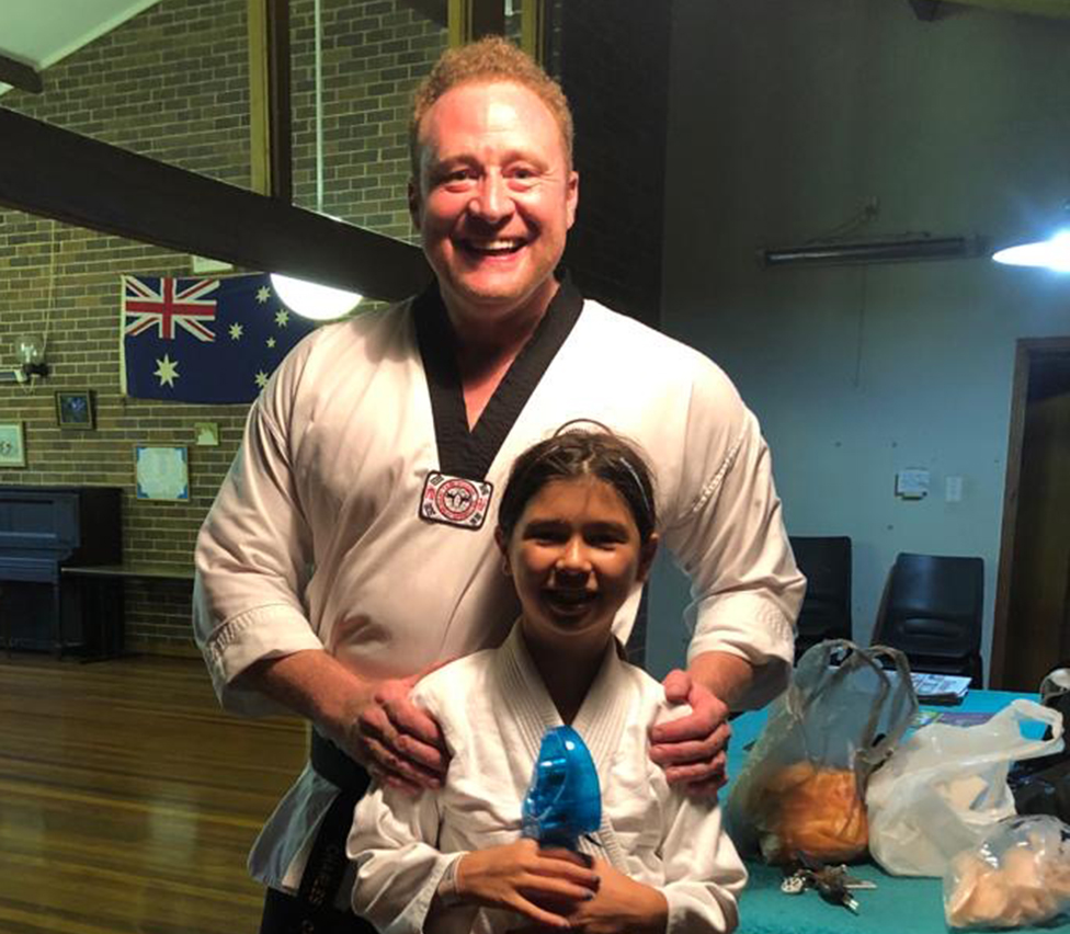 Charles with his daughter in martial arts uniform
