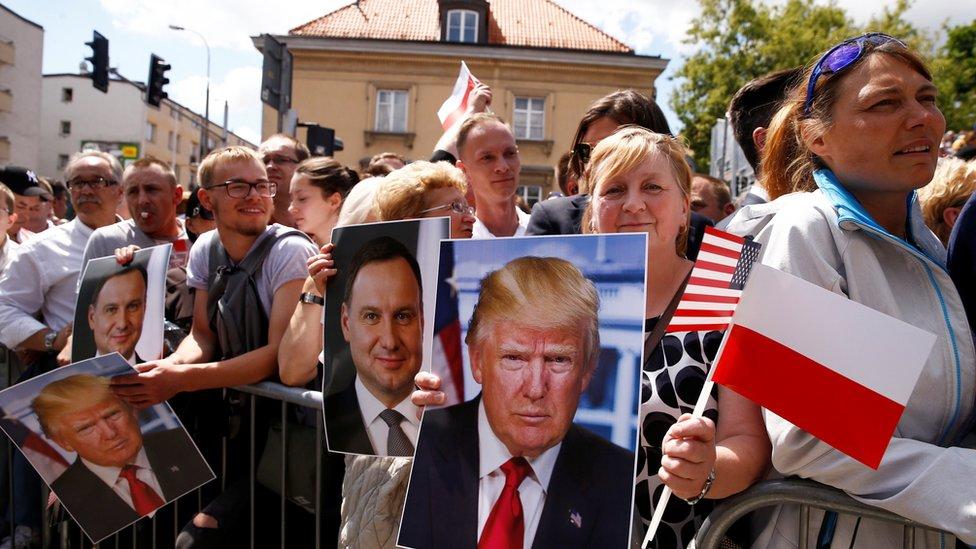 Gente con carteles de Trump y Duda.