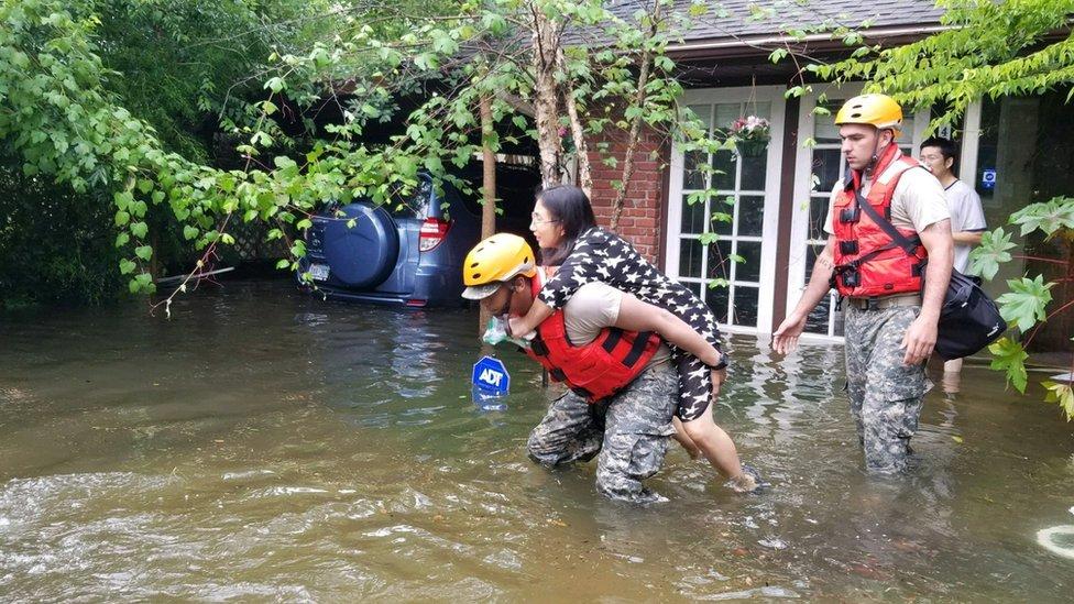 عناصر الإنقاذ يحملون امرأة لينقذوها من الفيضانات