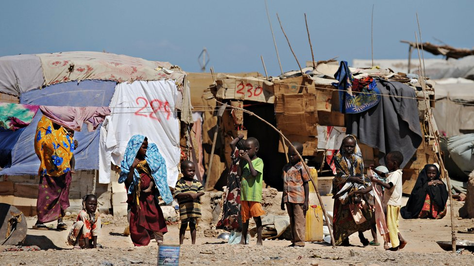 Women and children stand in front of their makeshift shelters at a camp for Internally Displaced People in Bossaso, a town in the northern breakaway state of Puntland, on 20 October 2009.