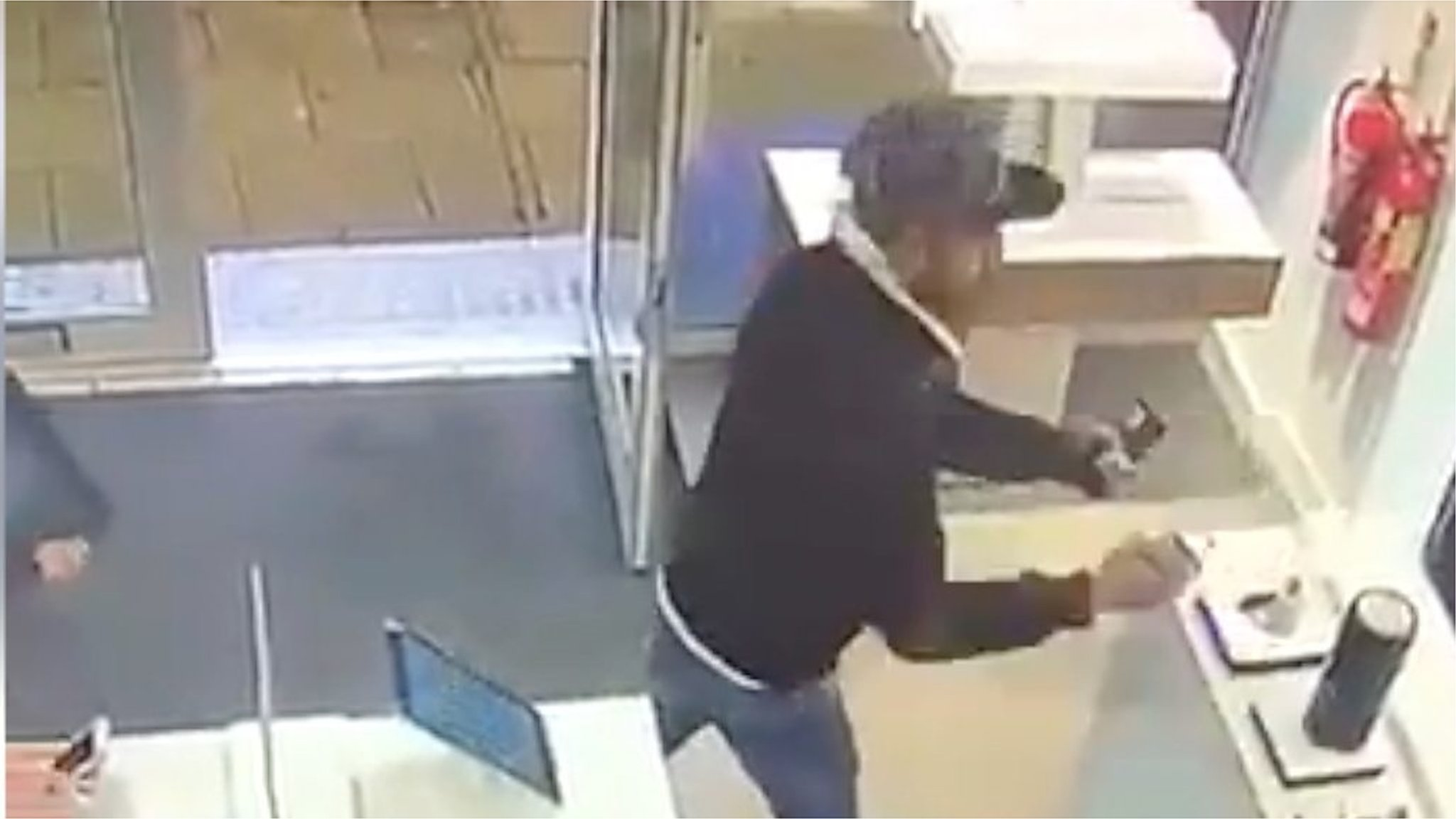 Phone shop staff watch as thief rips mobiles from shelf