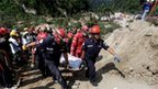 Rescue team members carry the body of a landslide victim in Santa Catarina Pinula, on the outskirts of Guatemala City, October 2, 2015.