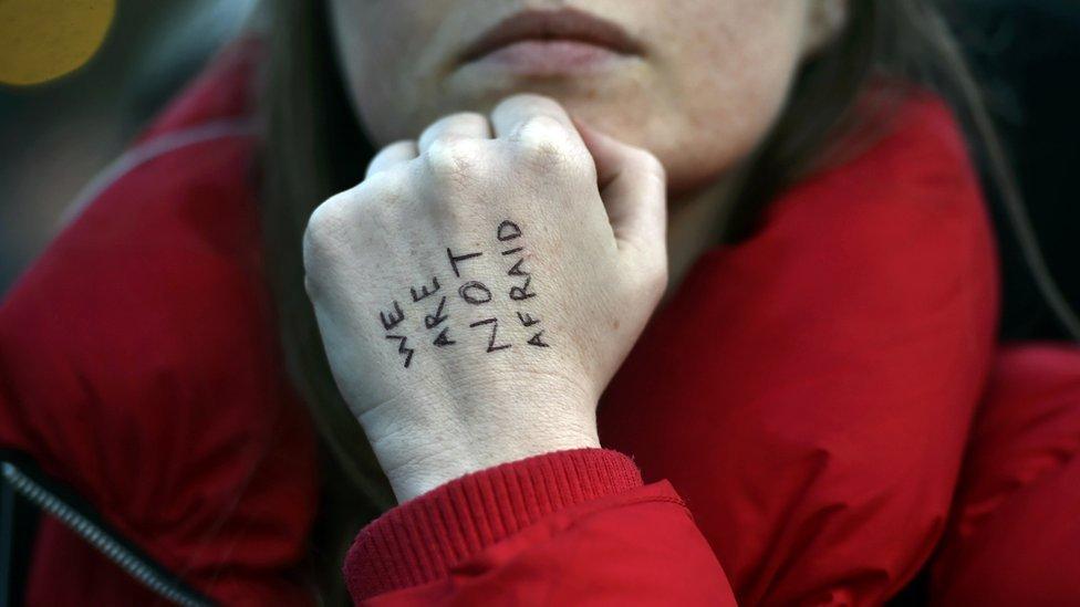 """Mujer enseñando un mensaje escrito en su mano que dice """"No tenemos miedo""""."""