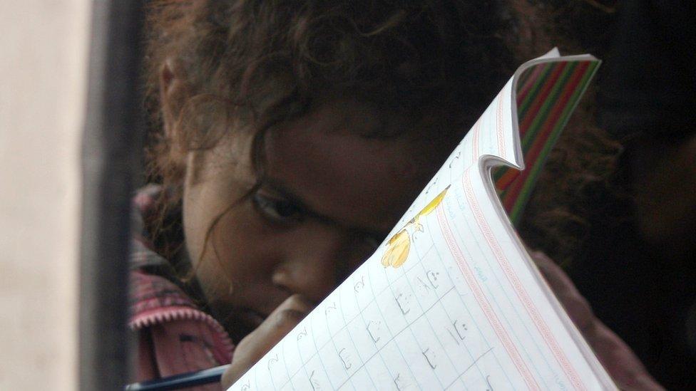 Una niña yemení lee un libro de texto.