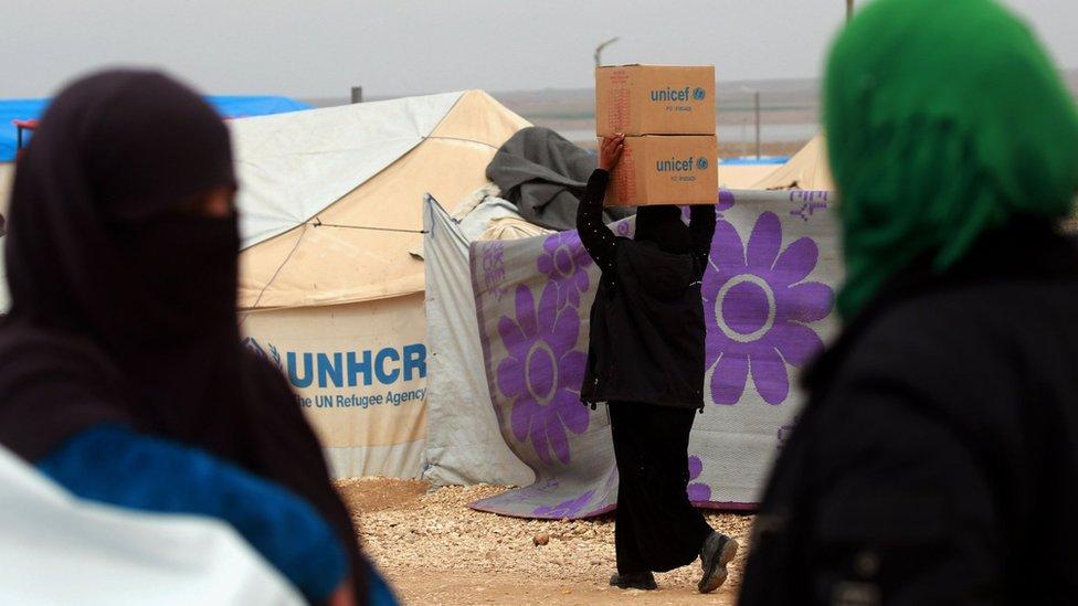 Una mujer carga cajas de asistencia humanitaria entregada por UNICEF, en un campo de refugiados en las zona de Hassakeh, en Siria, febrero 26 de 2018.