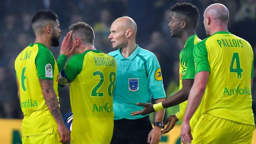 Tony Chapron es rodeado por jugadores del Nantes