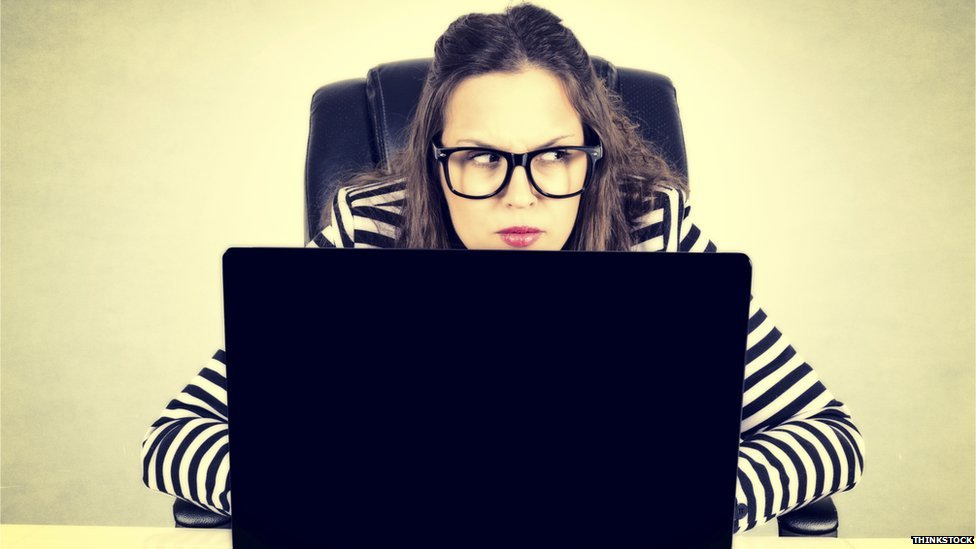 woman with laptop looking suspicious