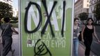 "People walk past a YES poster sprayed with a graffiti reading "" NO""  in Athens on 2 July 2015."