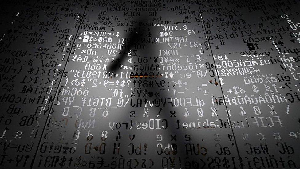 Foto de archivo que muestra a una persona que camina detrás de una pared de vidrio que muestra símbolos de codificación (17 de octubre de 2016)