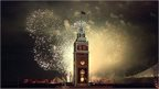 Fireworks behind a clock tower with 50 on in lights