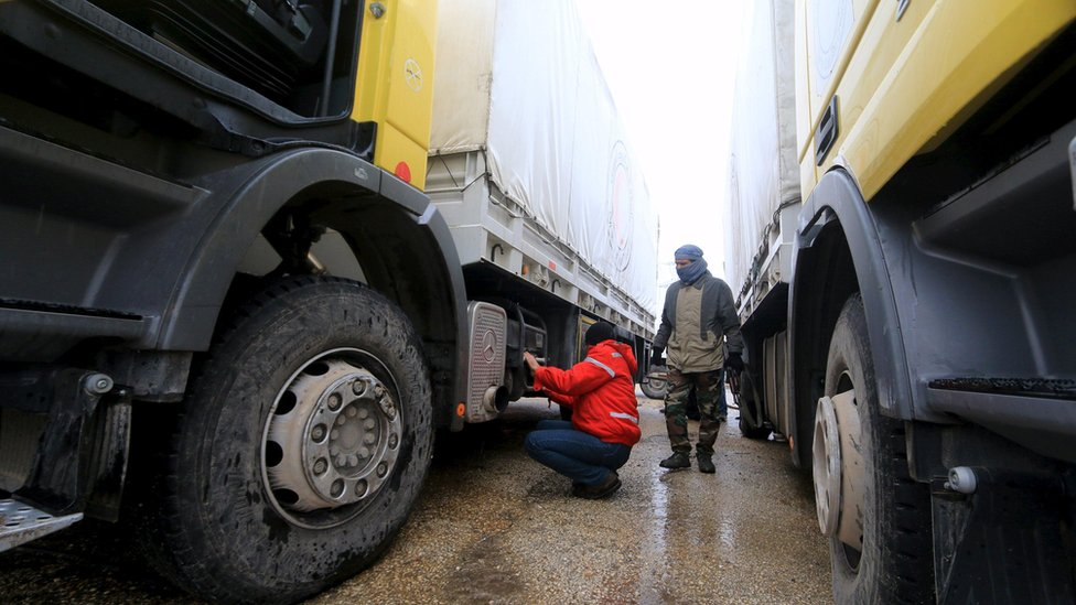 Rebel fighter inspects Red Crescent vehicles on their way to Foua and Kefraya, Syria (11 January)