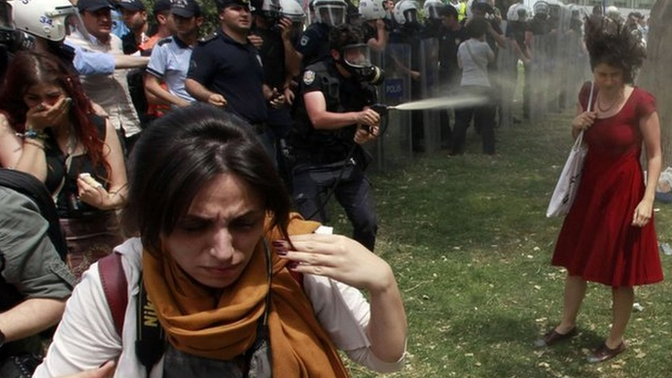 Una mujer vestida de rojo enfrenta a la policía en Turquía.