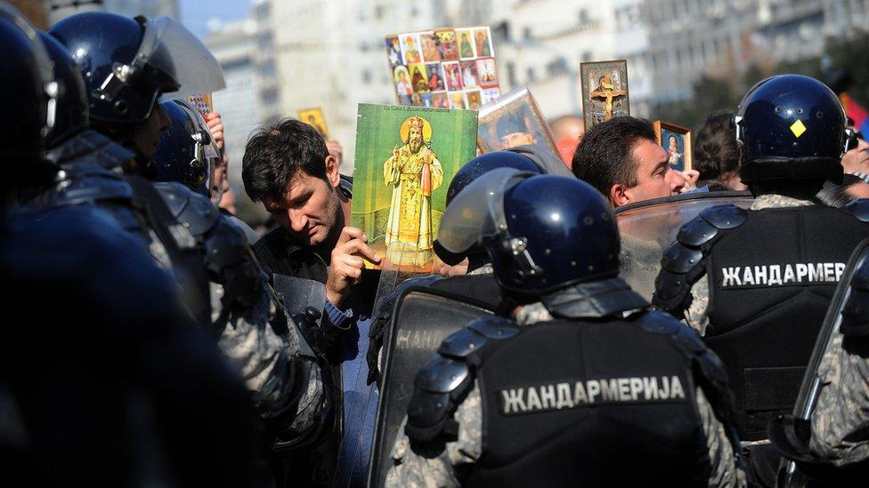 Un manifestante anti gay sostiene un ícono ortodoxo frente a la policía antimotines, durante el desfile de Orgullo Gay en Belgrado, el 10 de octubre de 2010.
