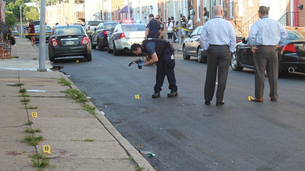 Detektif polisi Baltimore di lokasi pembunuhan di lingkungan Pigtown pada hari Sabtu