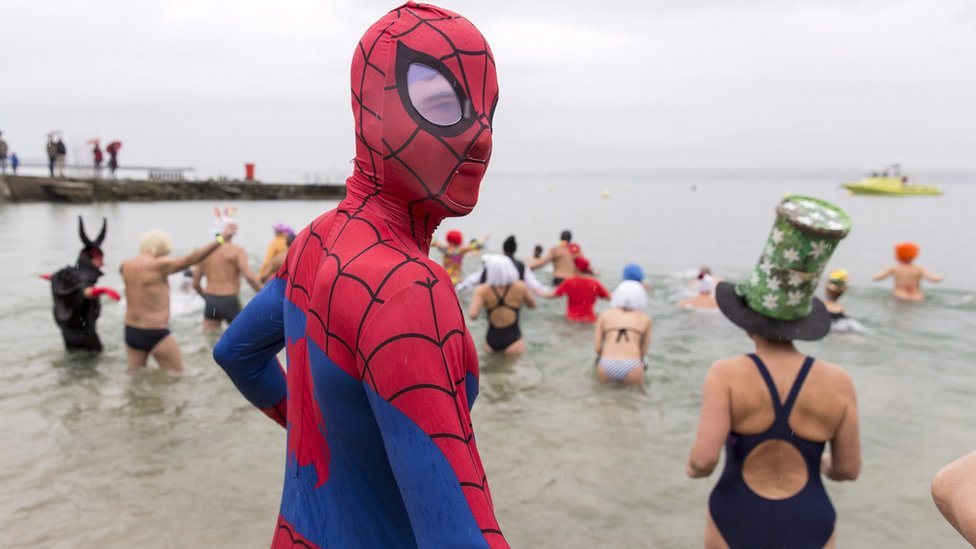 A person dressed in a Spiderman costume and others walk into Lake Geneva