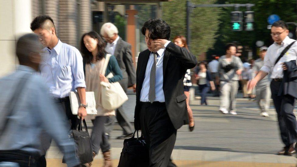 موظفون يابانيون يتوجهون إلى أعمالهم
