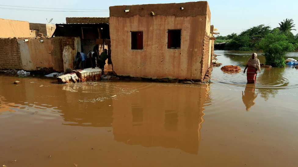 Residents walk through floodwaters from the Blue Nile as it submerges their neighborhood in the Al-Ikmayr area of Omdurman in Khartoum