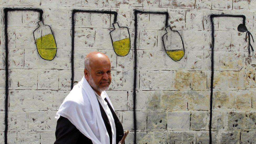 A Yemeni walks past graffiti depicting intravenous drips on a wall in Sanaa, Yemen (23 May 2017)