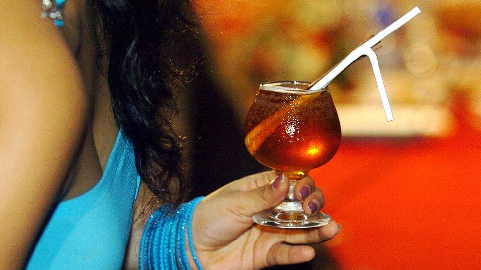 امرأة تحمل كأس