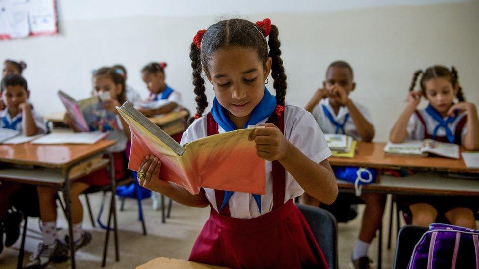 Niña cubana leyendo en clase