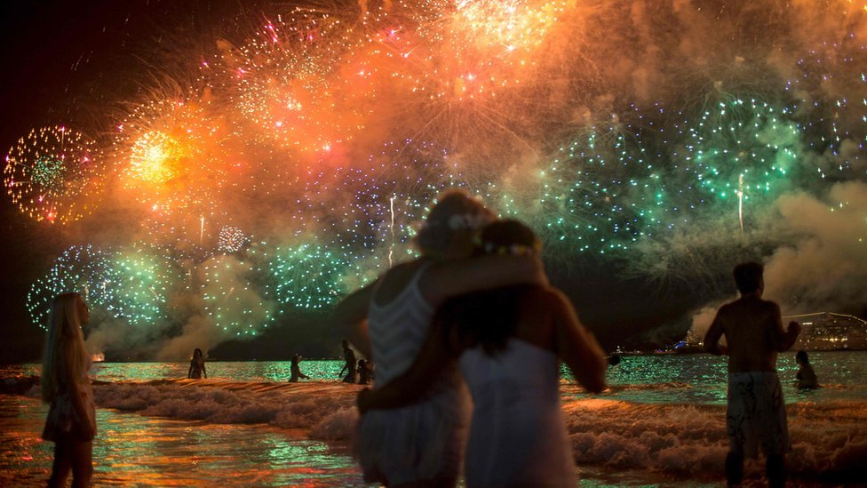 People watch fireworks during New Year's celebrations at Copacabana beach in Rio de Janeiro on January 1, 2018