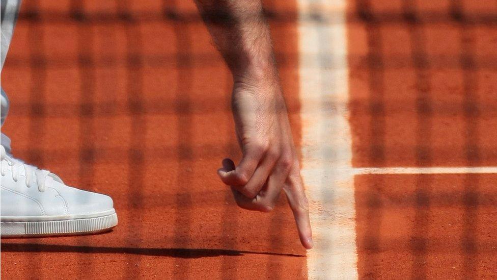 Juez señalando la marca de una pelota